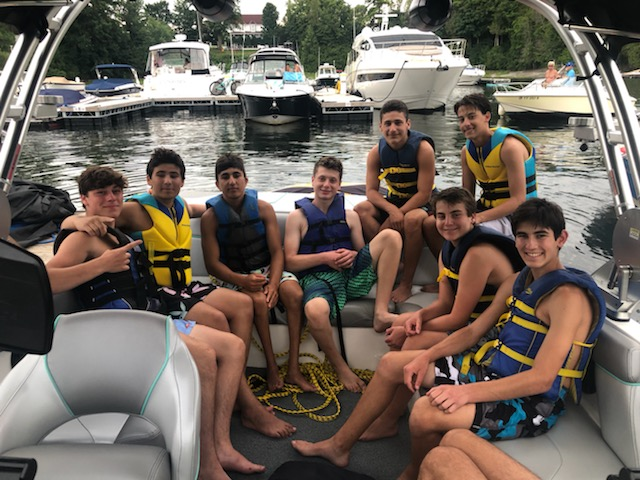 students on boat on lake