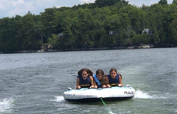 girls tubing on lake