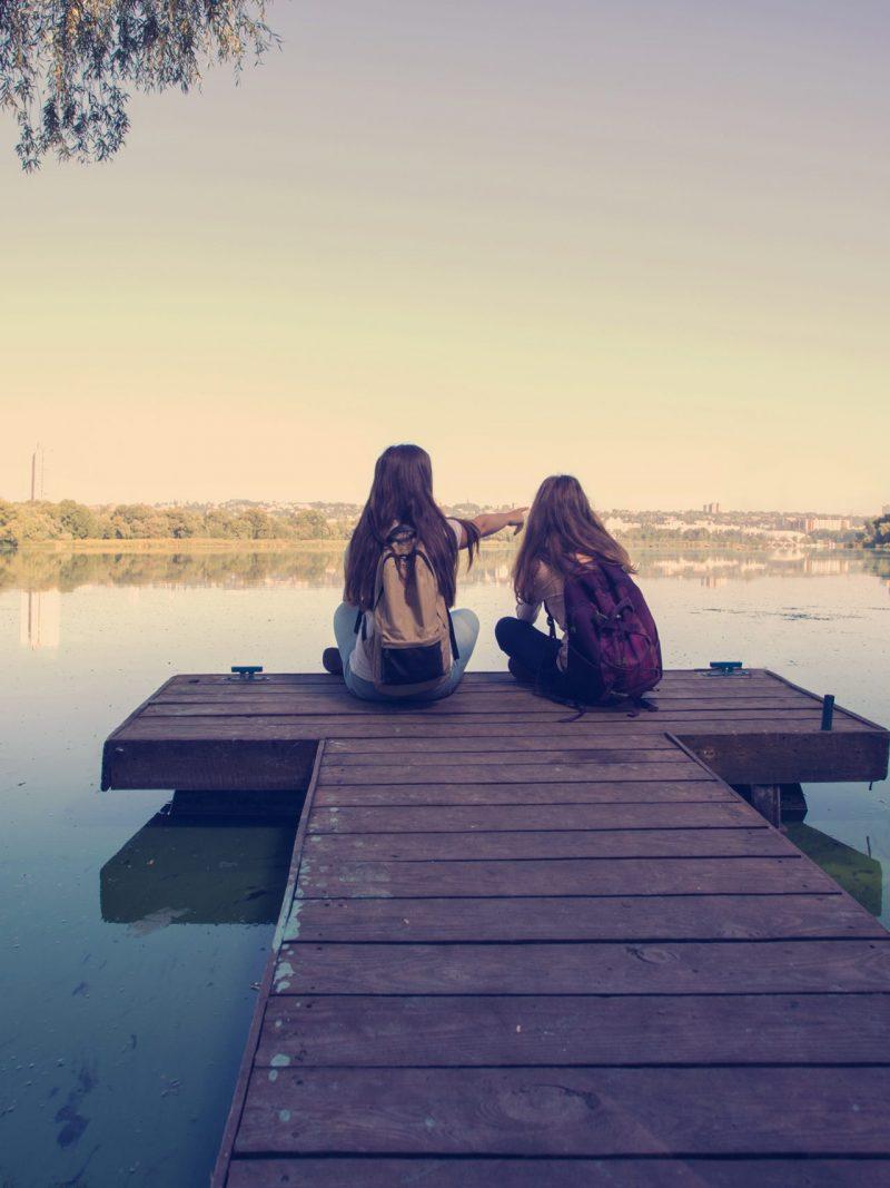 girls sitting on doc on Lake